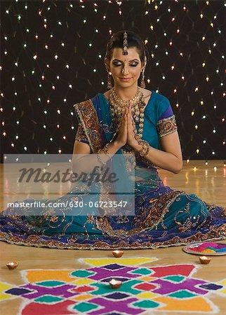Woman in prayer position near rangoli at Diwali festival