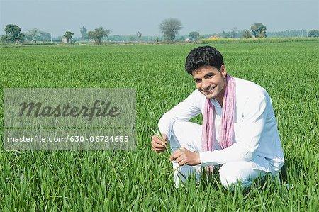 Farmer crouching in the field, Sonipat, Haryana, India