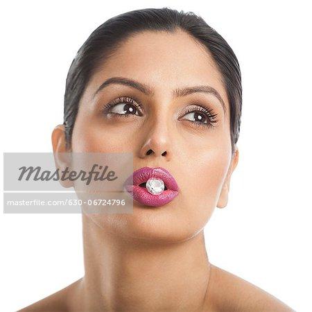 Woman holding diamond between her lips