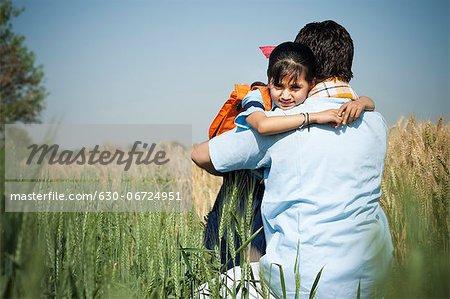 Farmer hugging his daughter in the field, Sohna, Haryana, India