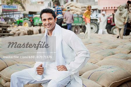 Man sitting on stack of wheat sacks in a grain market, Anaj Mandi, Sohna, Gurgaon, Haryana, India