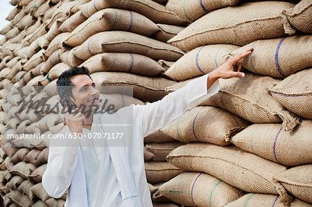 Man standing near sacks of wheat and talking on a mobile phone, Anaj Mandi, Sohna, Gurgaon, Haryana, India