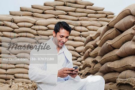 Man sitting on sack of wheat grains reading a SMS on mobile phone, Anaj Mandi, Sohna, Gurgaon, Haryana, India