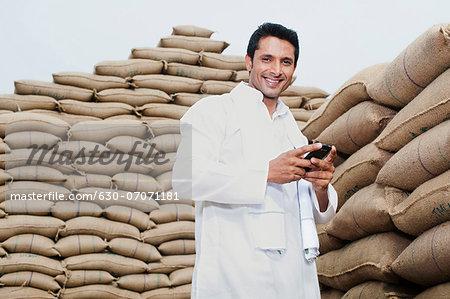Man standing near stacks of wheat sack holding a mobile phone, Anaj Mandi, Sohna, Gurgaon, Haryana, India