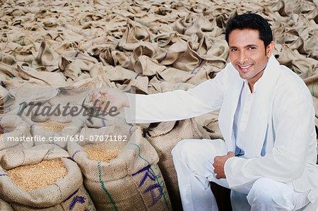 Man sitting near sacks of wheat and showing wheat grains, Anaj Mandi, Sohna, Gurgaon, Haryana, India