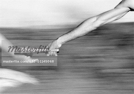 Male athletes passing relay baton, close-up, b&w