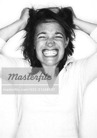 Woman gritting teeth, pulling hair, portrait