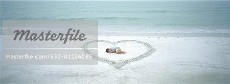 Child lying inside heart drawn on beach