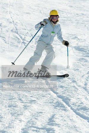 Teenage girl skiing down ski slope, full length