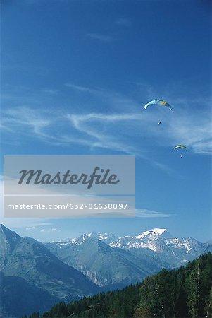Paragliders in mountainous landscape