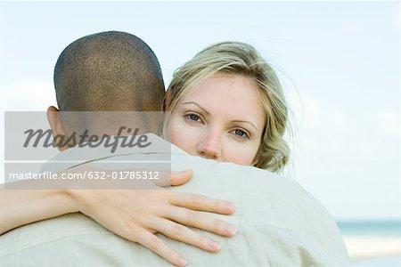 Woman embracing man, looking over his shoulder at camera