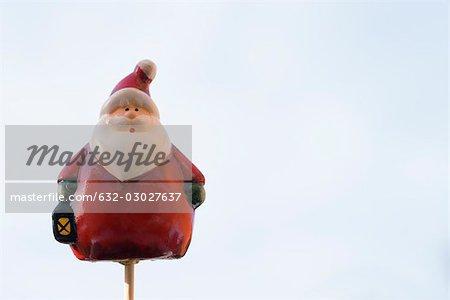 Santa Claus figurine on thin wooden post