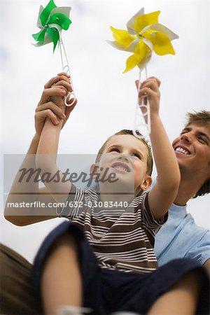 Little boy sitting on father's lap, both holding pinwheels