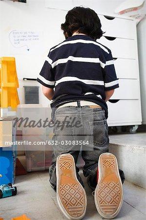 Little boy kneeling on floor in front of plastic bin, rear view