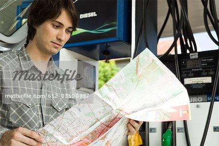Man checking map at gas station