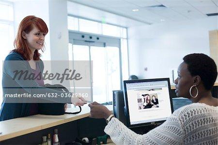 Female customer handing credit card to receptionist