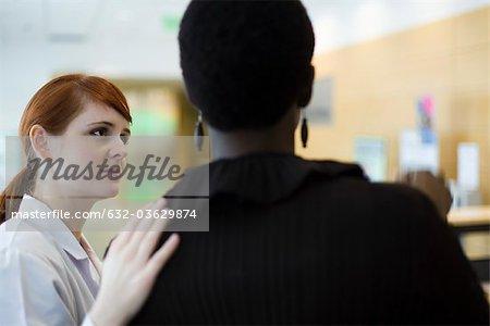 Female healthcare worker putting hand on patient's shoulder