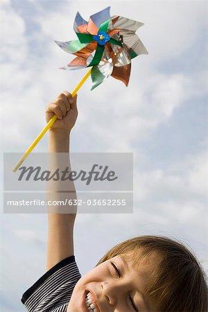 Boy holding pinwheel triumphantly in air