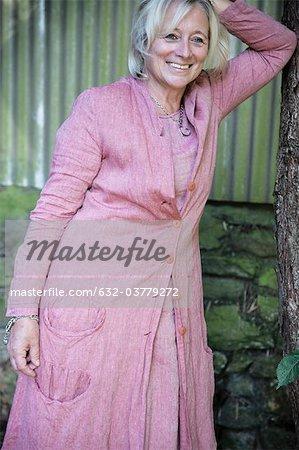 Mature woman leaning against tree trunk, portrait