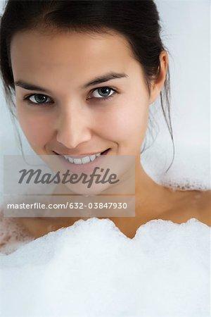 Woman relaxing in bubble bath, portrait