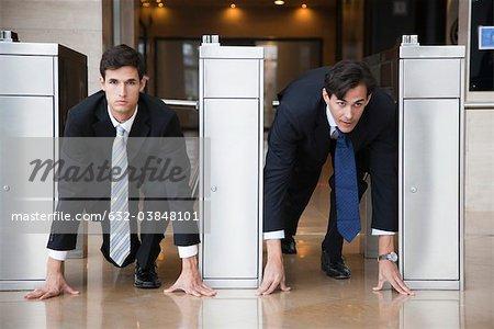Businessmen crouching in starting position in lobby turnstiles