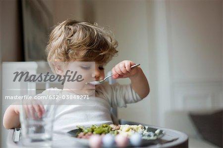 Toddler boy feeding himself with spoon