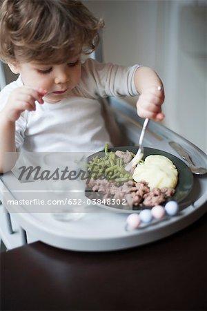 Toddler boy feeding himself