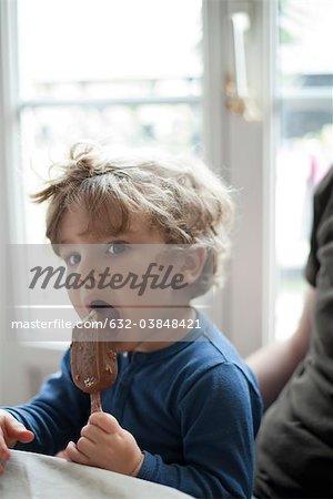 Toddler boy eating ice cream bar