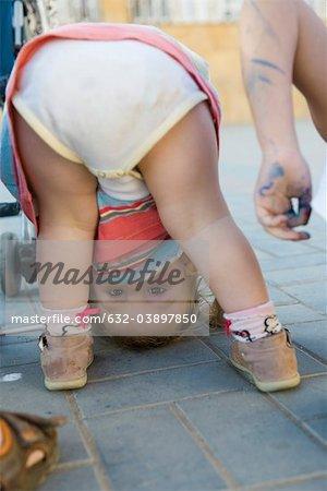 Toddler girl bending over, peeking through legs at camera