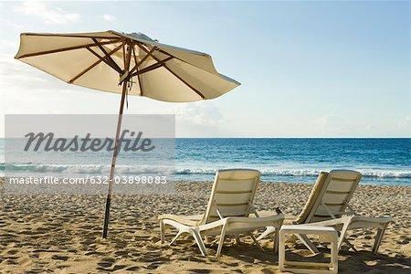 Beach umbrella and deckchairs on beach