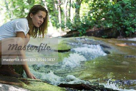Female hiker crouching beside stream