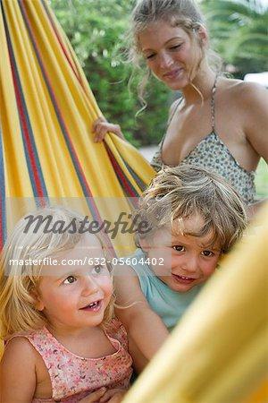 Mother watching children in hammock