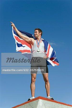Male athlete on winner's podium, holding up British flag