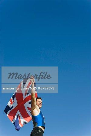 Male athlete holding up British flag