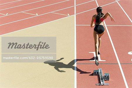 Female runner on track, rear view