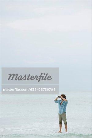 Man standing in sea, looking through binoculars