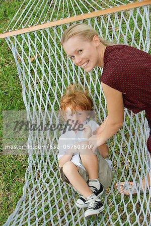 Mother tickling son in hammock