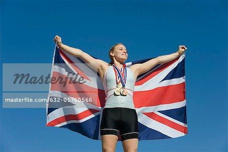 Female athlete being honored on podium, holding up British flag