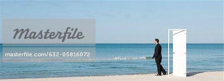 Businessman standing on beach next to half-open door, looking at ocean