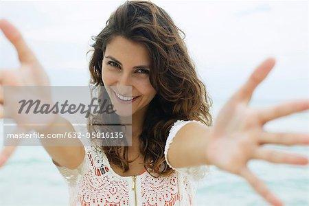 Woman reaching arms toward camera, smiling