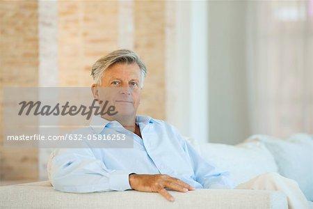 Senior man sitting on sofa, portrait