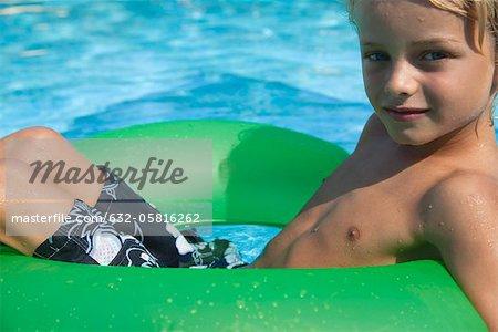 Boy relaxing on float in pool, portrait