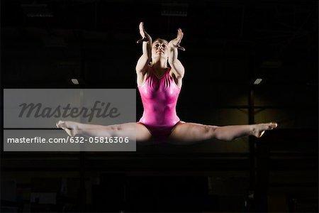 Female gymnast doing splits in midair