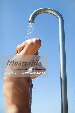 Man using outdoor shower