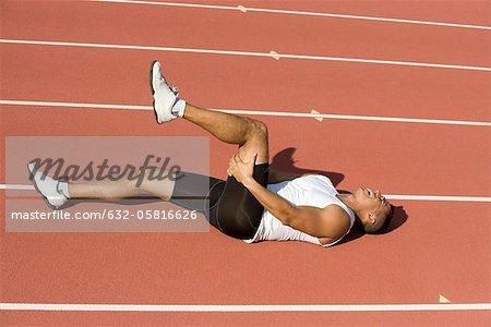 injured runner lying on running track stock photo masterfile