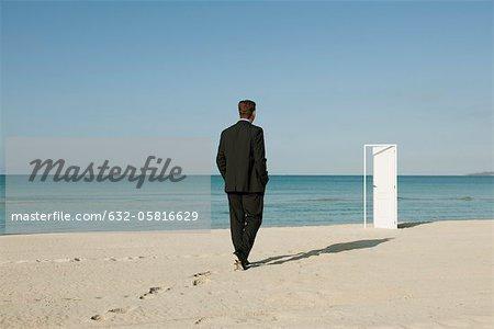 Businessman walking on beach towards half-open door in background