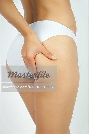 Woman pinching body fat on buttocks, cropped