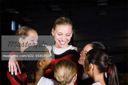 Team of female gymnasts embracing