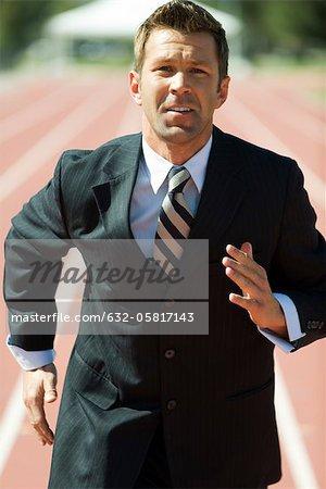 Businessman running on track