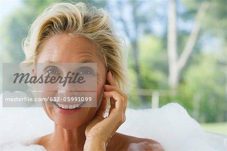 Mature woman relaxing in bubble bath, portrait